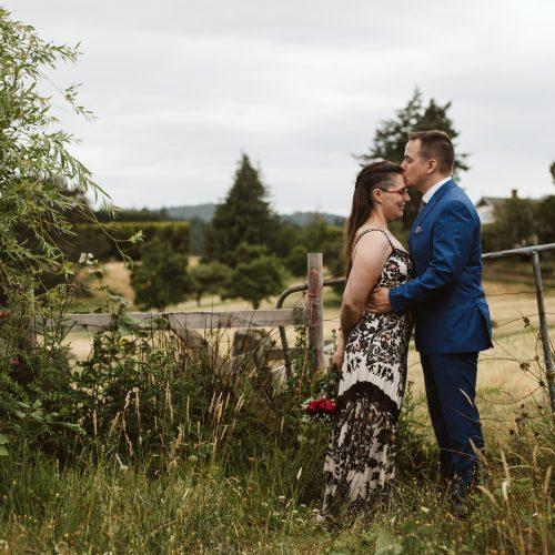 Bride and groom sweet moment walking in field. Sea Tree Weddings.